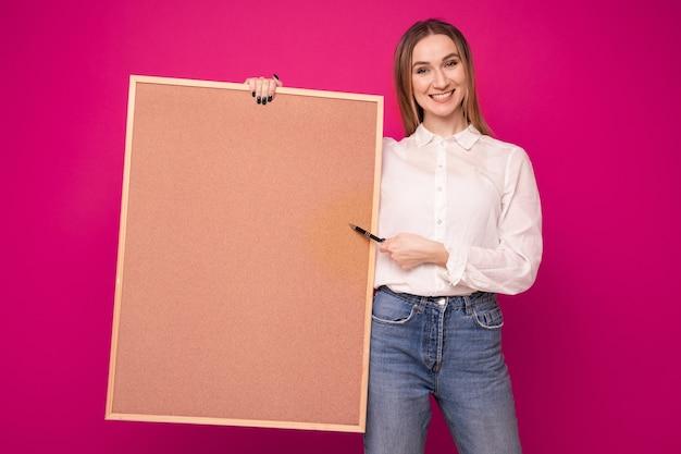 Portrait d'une jeune femme dans une chemise blanche tenant un tableau de tâches sur fond rose