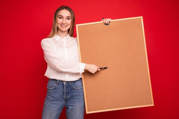 Portrait d'une jeune femme dans une chemise blanche tenant un tableau de tâches sur fond rouge