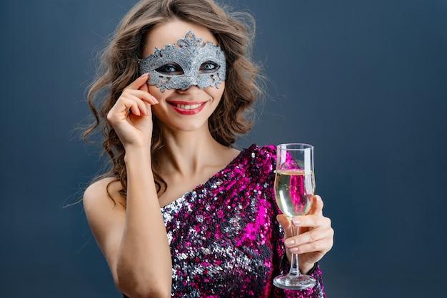 Portrait d'une jeune femme dans un masque de carnaval avec un verre de champagne surélevé souriant gros plan