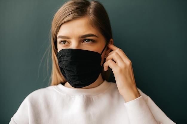 Portrait d'une jeune femme dans un masque noir médical isolé. covid-19, arrêtez le coronavirus.