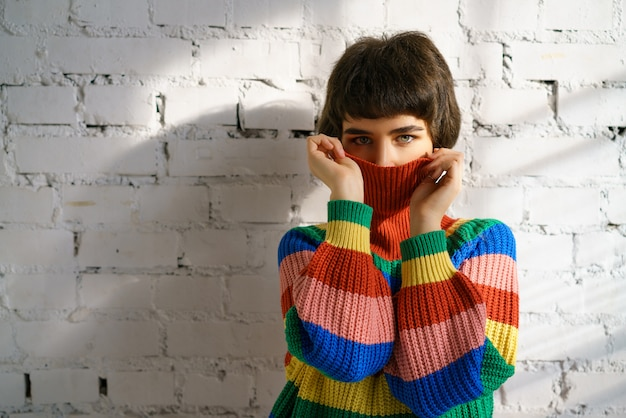 Portrait d'une jeune femme dans un pull multicolore, couvrant son visage avec un pull. le concept de timidité