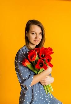 Portrait d'une jeune femme dans une robe bleue avec un bouquet de tulipes rouges sur un mur jaune