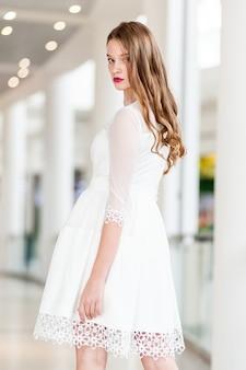 Portrait d'une jeune femme dans une robe courte blanche