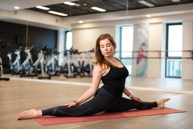 Portrait de jeune femme dans la salle de gym assis sur le grand écart. mode de vie en forme et bien-être