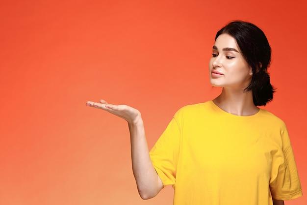 Portrait de jeune femme dans un t-shirt jaune en regardant sa main sur fond orange