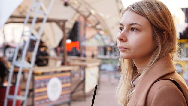 Portrait d'une jeune femme dans la ville. aire de restauration urbaine avec cuisine de rue. portrait d'une blonde. photo de style de vie