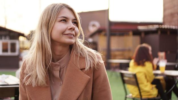 Portrait d'une jeune femme dans la ville. aire de restauration urbaine avec cuisine de rue. portrait d'une blonde souriante. photo de style de vie