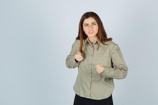 Portrait de jeune femme debout dans une pose de combat, serrant les dents en chemise, jupe et regardant la vue de face en colère