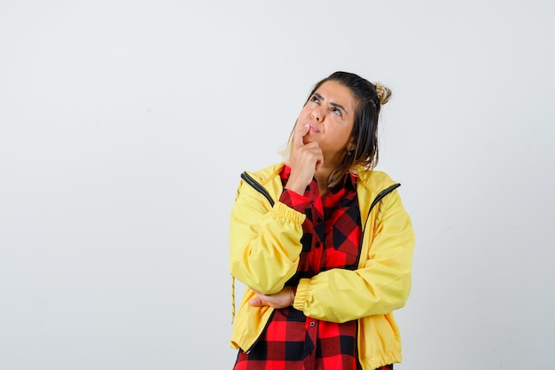 Portrait de jeune femme debout dans une pose de réflexion, levant les yeux en chemise à carreaux, veste et regardant perplexe vue de face