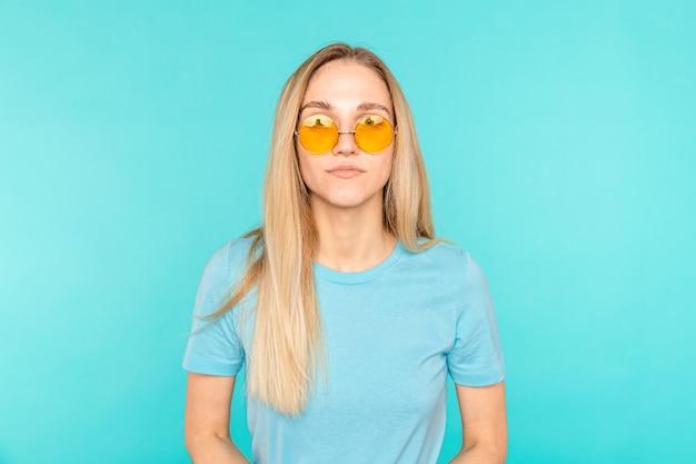 Portrait de jeune femme debout sur fond bleu.