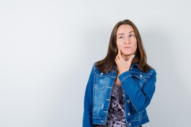 Portrait de jeune femme debout en pensant pose en chemisier, veste en jean et à la vue de face pensive