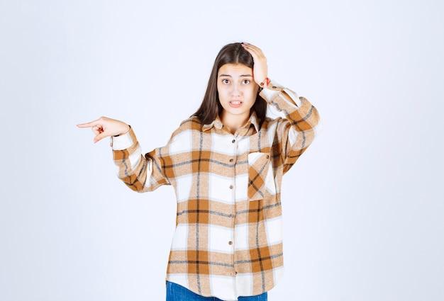 Portrait de jeune femme debout et pointant quelque part sur un mur blanc.