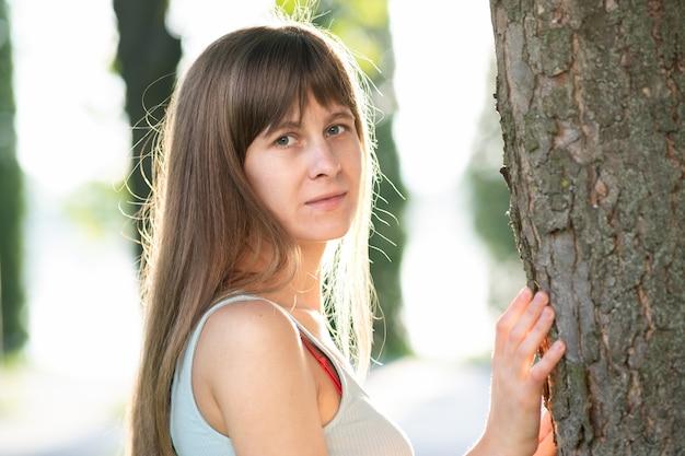 Portrait de jeune femme debout près d'un arbre