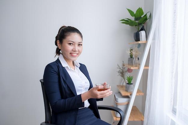 Portrait de jeune femme debout avec une tasse de thé au bureau