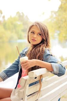 Portrait de jeune femme décontractée, boire un café en plein air