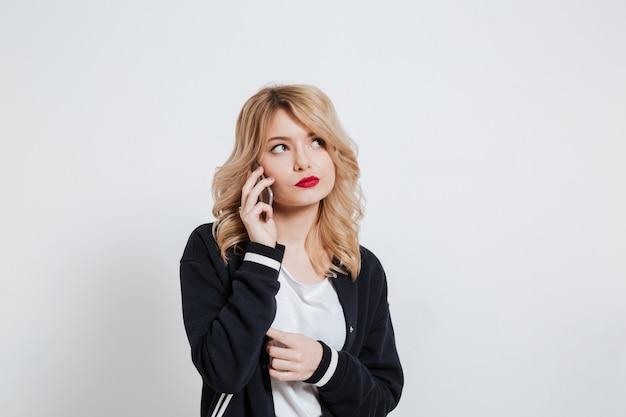 Portrait d'une jeune femme décontractée bouleversée, parler au téléphone