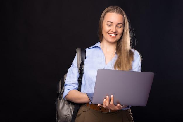Portrait d'une jeune femme décontractée souriante utilisant un ordinateur portable et portant un sac à dos