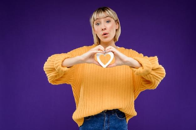 Portrait de jeune femme avec décor coeur sur mur violet