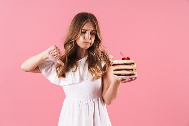 Portrait d'une jeune femme déçue vêtue d'une robe blanche se mordant la lèvre tenant un morceau de gâteau avec le pouce vers le bas isolé sur un mur rose