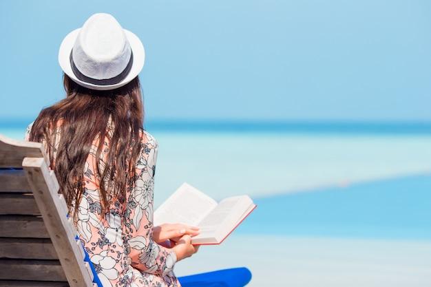 Portrait, jeune, femme, délassant, plage, lecture livre