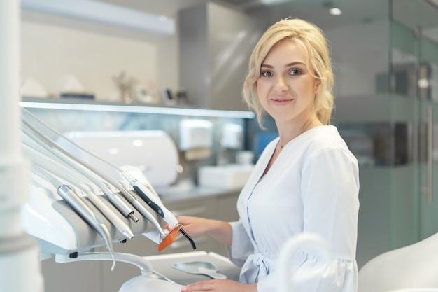 Portrait de jeune femme dentiste souriante dans un cabinet dentaire moderne.