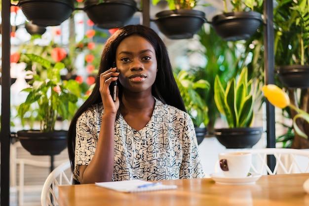 Portrait d'une jeune femme détendue assise au café en plein air, parler au téléphone portable