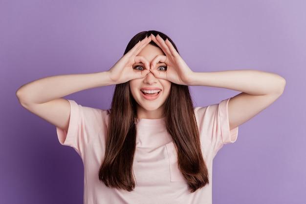 Portrait de jeune femme drôle montrant les yeux de couverture de signe ok