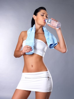 Portrait de jeune femme eau potable avec serviette