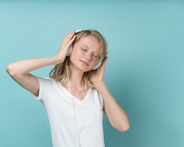 Portrait de jeune femme à l'écoute de la musique via des écouteurs sur ton neutre de couleur aqua menthe
