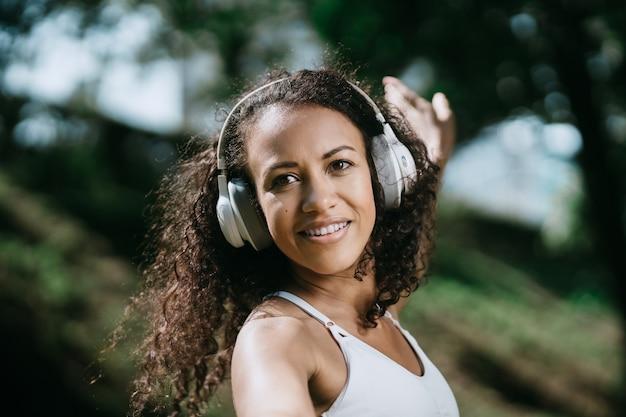 Portrait d'une jeune femme avec des écouteurs sur le fond de n