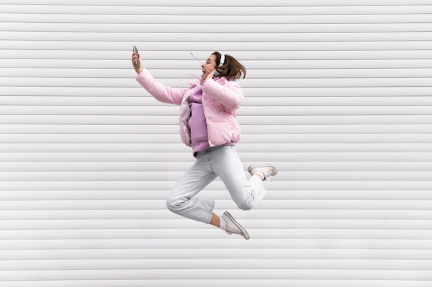 Portrait, jeune femme, à, écouteurs, sauter