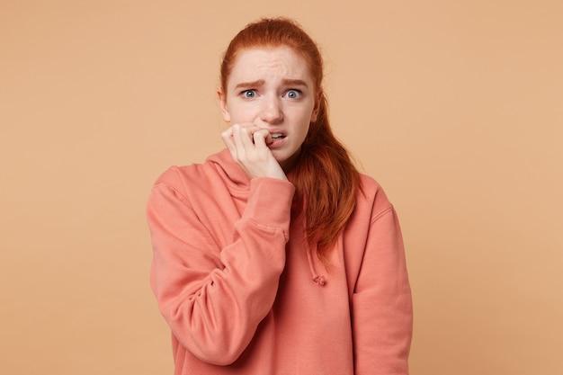 Portrait d'une jeune femme effrayée aux yeux bleus et cheveux rouges réunis en une queue de cheval