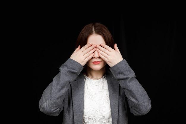 Portrait d'une jeune femme effrayée couvrant les yeux avec les mains