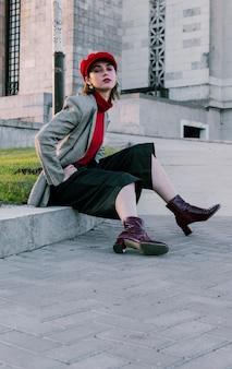 Portrait d'une jeune femme élégante assis près de l'herbe verte