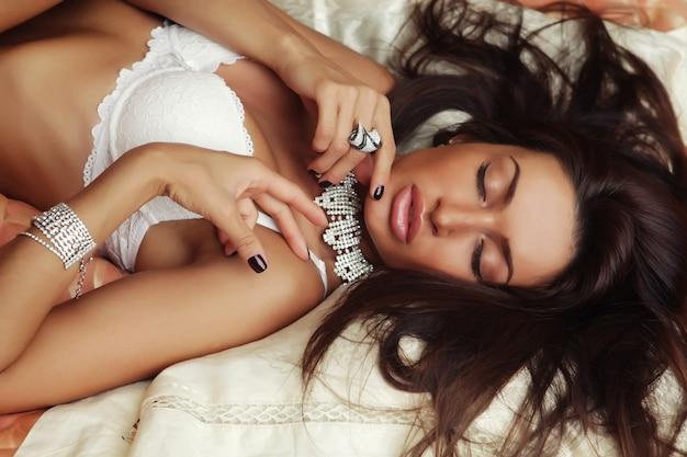 Portrait de jeune femme élégante au lit