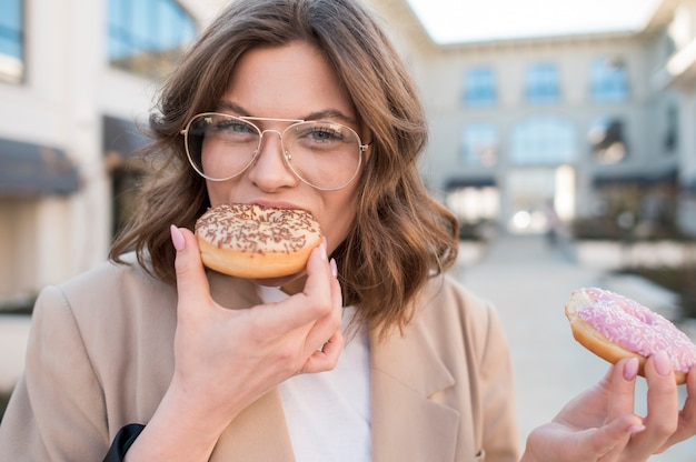 Portrait de jeune femme élégante, manger des beignets