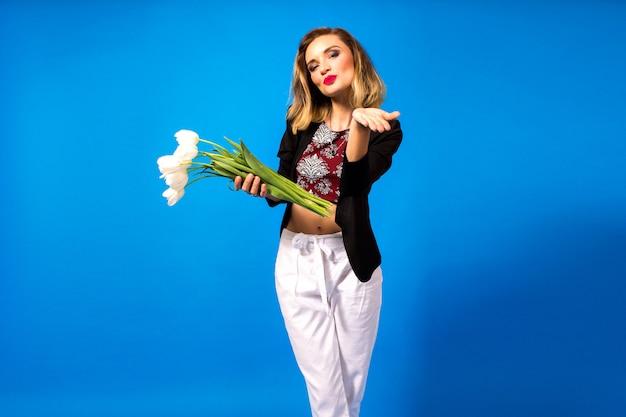 Portrait de jeune femme élégante avec maquillage lumineux et blazer sombre, tenant des fleurs blanches