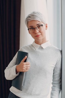 Portrait de jeune femme élégante en pull blanc et lunettes avec ordinateur portable debout près de la fenêtre
