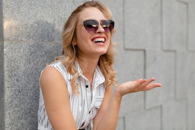 Portrait de jeune femme élégante et séduisante souriant marchant dans la rue de la ville en robe de style mode d'été portant des lunettes de soleil sourire candide