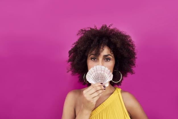 Portrait d'une jeune femme, elle tient un coquillage dans ses mains.