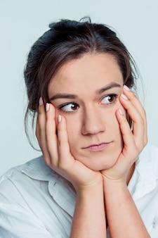 Le portrait de la jeune femme avec des émotions réfléchies