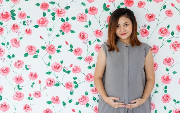 Portrait de jeune femme enceinte asiatique souriant debout touchant son ventre en regardant une caméra sur fond de roses blanches. concept de dame saine et heureuse.