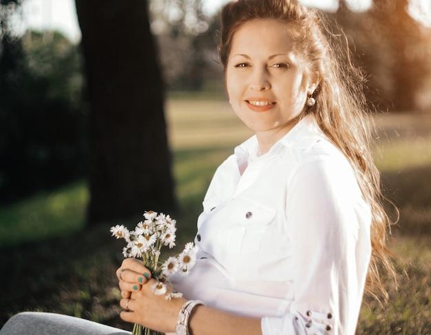 Portrait de jeune femme enceinte avec un bouquet. fleurs sauvages dans