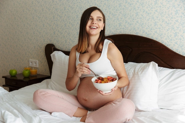 Portrait d'une jeune femme enceinte qui rit