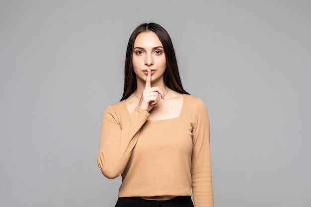 Portrait d'une jeune femme enjouée montrant un geste de silence et un clin d'œil isolé sur le mur gris