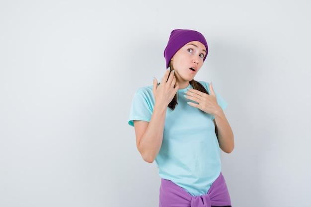 Portrait de jeune femme entendant une conversation privée en t-shirt, bonnet et regardant la vue de face curieuse