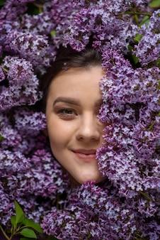 Portrait d'une jeune femme entourée de lilas. une femme regarde dans le cadre. le sexe du visage est couvert de lilas.