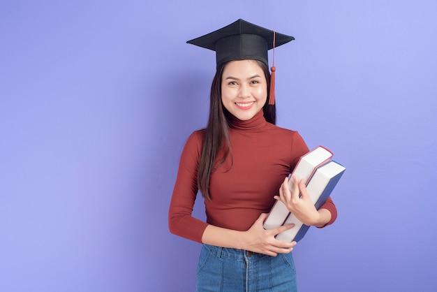 Portrait de jeune femme étudiante universitaire avec chapeau de graduation sur violet