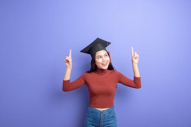 Portrait de jeune femme étudiante à l'université avec chapeau de graduation sur fond violet