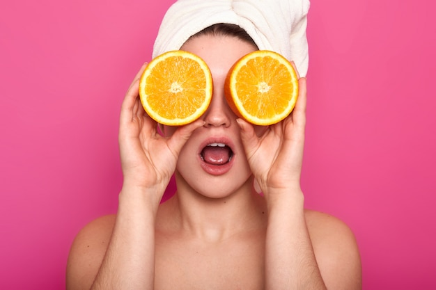 Portrait de jeune femme européenne choquée agréable contre les yeux avec des oranges, a une serviette blanche sur la tête. modèle à peau claire pose en studio isolé sur rose. concept de beauté.